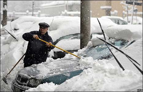 A man removes snow from his car in Milan 7 January 2009