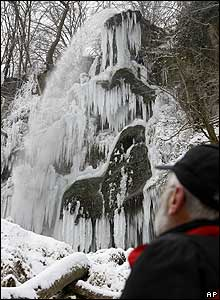 A man looks at icicles hanging from a waterfall in Bad Urach, Germany, 7 Jan 2009