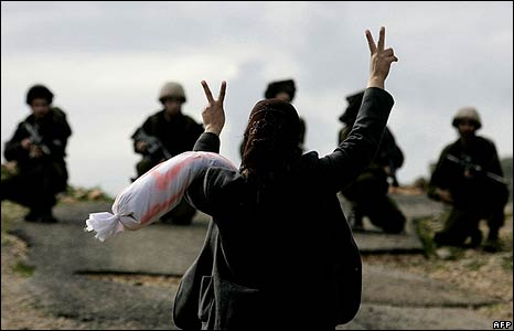 "A Palestinian woman flashes the ""V"" for victory sign at Israeli soldiers in Bilin village, West Bank on 8/1/09"