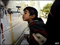 Una mujer palestina ayuda a un ni�o a tomar agua.