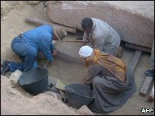 Zahi Hawass and other excavators attend to sarcophagus