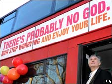 Richard Dawkins beside atheist bus poster