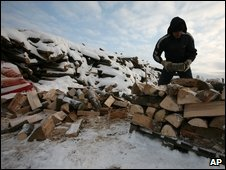 A man arranges a pile of firewood at a wood market near the Bulgarian capital Sofia