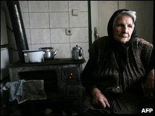 An elderly woman warms herself near a stove in the Bulgarian capital Sofia, 8 January