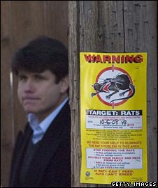 Rod Blagojevich behind a sign warning of rats