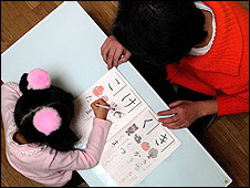A man helps a child with her homework (Photo: Alfie Goodrich)