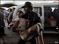 Una ni�a es cargada para ser ingresada en el hospital