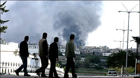 Palestinian youths watch smoke billow from burning factories after Israeli strikes in the east of Gaza city, Gaza Strip on 9 January 2009
