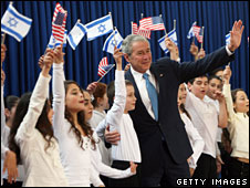 George W Bush  is greeted by a crowd of Israeli children waving American and Israeli flags as he arrives at the Israeli President's Residence in Jerusalem, 9 January, 2008