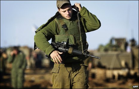 An Israeli soldier slings his rifle as he moves through a mechanised position on the Israeli side of the Israel-Gaza boundary on 10 January 2009