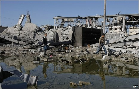 Palestinian boys walk past a destroyed building in Zeitun neighbourhood after Israeli strikes in Gaza City on 10 January 2009