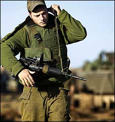 An Israeli soldier on the Israel-Gaza border slings his rifle
