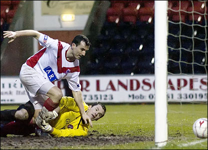 Simon Lynch (top) gets the better of Spartans keeper Chris Flockhart to extend Airdrie Utd's advantage to two goals