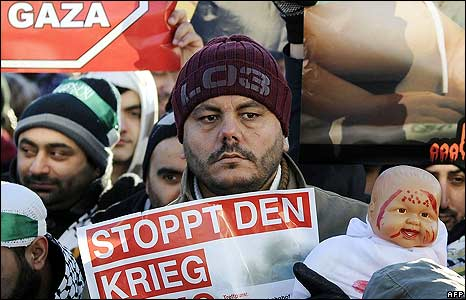 """A demonstrator in Germany holds a poster reading: """"Stop the war"""""""