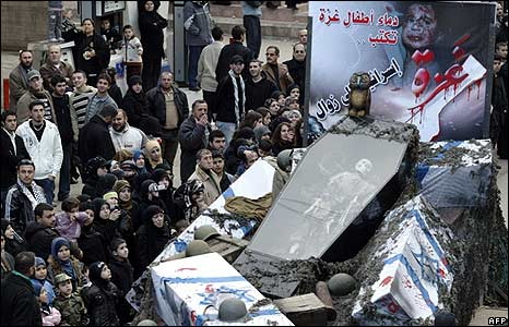Lebanese people watch a float depicting a coffin and a poster of a Palestinian child victim