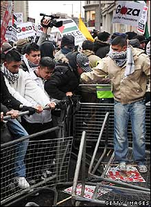 Protesters force their way through a barrier outside the Israeli embassy in London