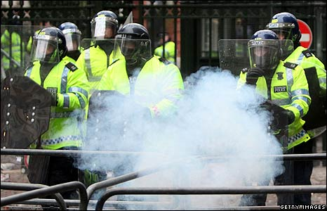 Police stand back as a firework is thrown at the Israeli embassy in London
