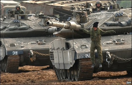 An Israeli soldier jumps down from a tank on the Israeli side of the Israel-Gaza border on 11 January 2009