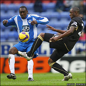 Ledley King attempts to tackle Heskey