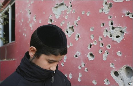An Israeli boy walks past a wall of a house that was hit by a shrapnel of a rocket fired from the Gaza Strip in the southern Israeli town of Beersheeba on 11 January 2009