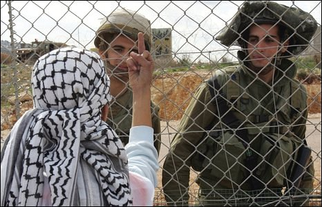 A Palestinian protestor makes a gesture to Israeli soldiers during a protest in the West Bank near Ramallah on 11 January 2009