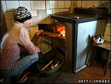 A woman puts a piece of wood in her house in Donetsk