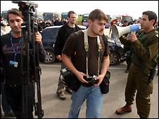 An Israeli military policeman orders journalists to move location on the Israeli side of the Erez border crossing  - 8/1/2009