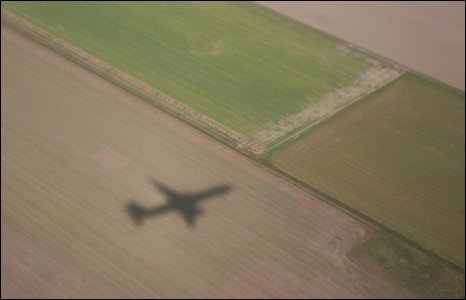 A plane cast a shadow on a field