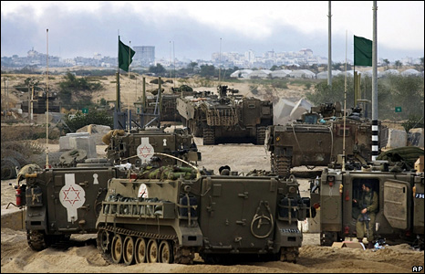Israeli military vehicles cross the Israel-Gaza border