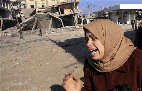 A Palestinian woman reacts to an air strike in Rafah