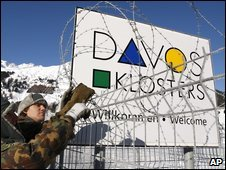 Members of the Swiss army place barbed wire on a fence to secure the area at the helicopter landing place in Davos-Dorf, Switzerland