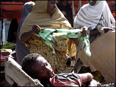An injured Somalis lies in a wheelbarrow