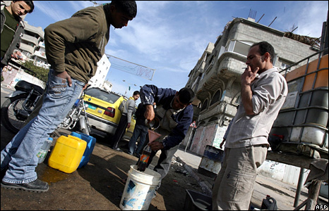Palestinians buy fuel in a street of Gaza City
