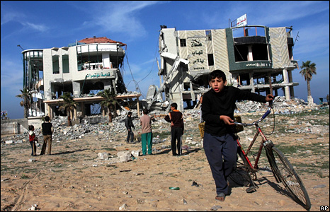 Palestinian children gather around the remains of two destroyed buildings in Gaza City