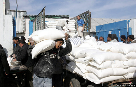 Palestinians unload food aid from the UN in the Shati refugee camp