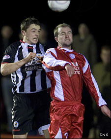 Stephen McGinn (left) challenges Richard Walker in the air