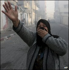 A Palestinian woman covers her face as smoke rises following an explosion caused by Israeli military operations in Gaza city on 14 January 2009