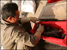 A worker wraps some of the remains in red cloth