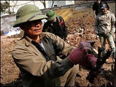 A man works at the site of the mass grave