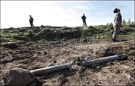Lebanese soldiers next to a rocket which fell short in southern Lebanon, several kilometres north of the Israeli border