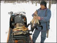 Охотник с добычей у снегохода (фото Дмитрия Климова)