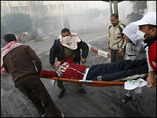 Palestinians carry a wounded man in a stretcher in Gaza City - 14/1/2009