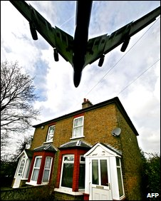 A plane flies over a house on its approach to Heathrow