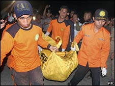 Indonesian rescuers carry the body of one of the victims of the ferry disaster