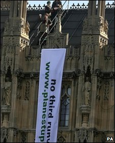 Anti-runway protesters hang a banner off the Houses of Parliament