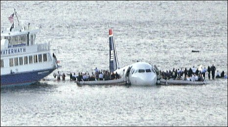 Passengers await rescue on the wings of the ditched aircraft