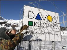 Members of the Swiss army place barbed wire on a fence in Davos