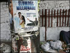 A man sleeps near a poster of Slumdog Millionaire in Mumbai on January 13, 2009