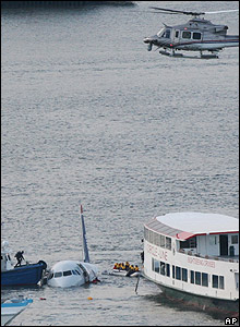 Passengers in an inflatable raft are rescued by ferry boats as a helicopter hovers above