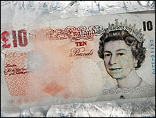 A ten pound note frozen in ice